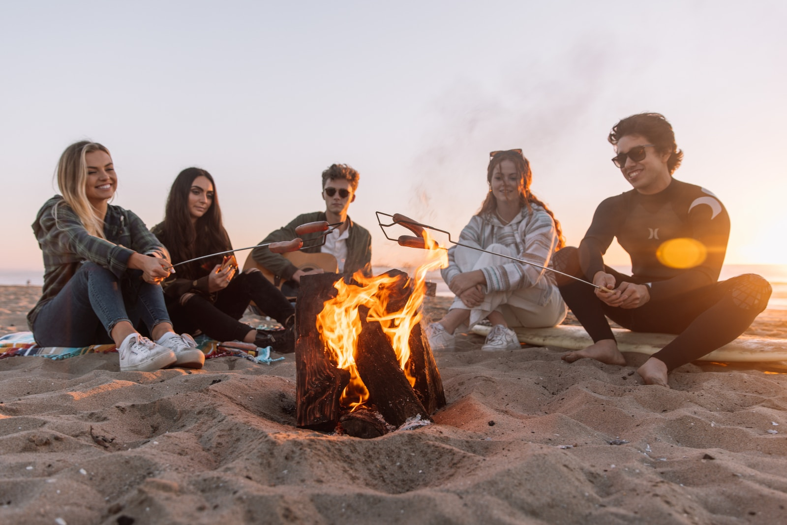 group of people sitting on ground with bonfire